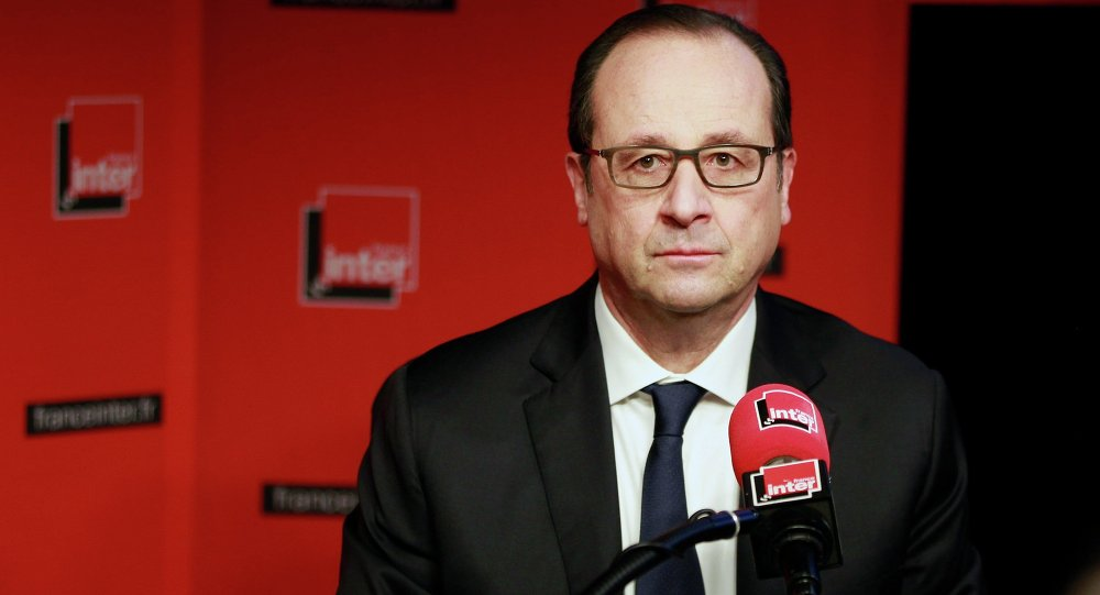 French President Francois Hollande prepares to answer journalists during a live interview at the France Inter radio station studios in Paris