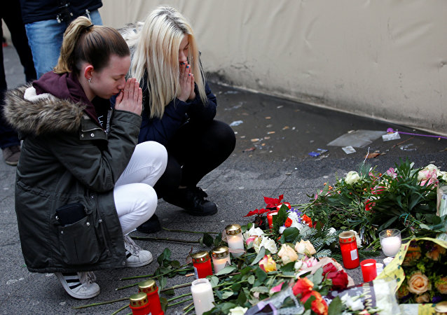 Women mourn at the scene where a truck ploughed into a crowded Christmas market in the German capital last night in Berlin, Germany, December 20, 2016