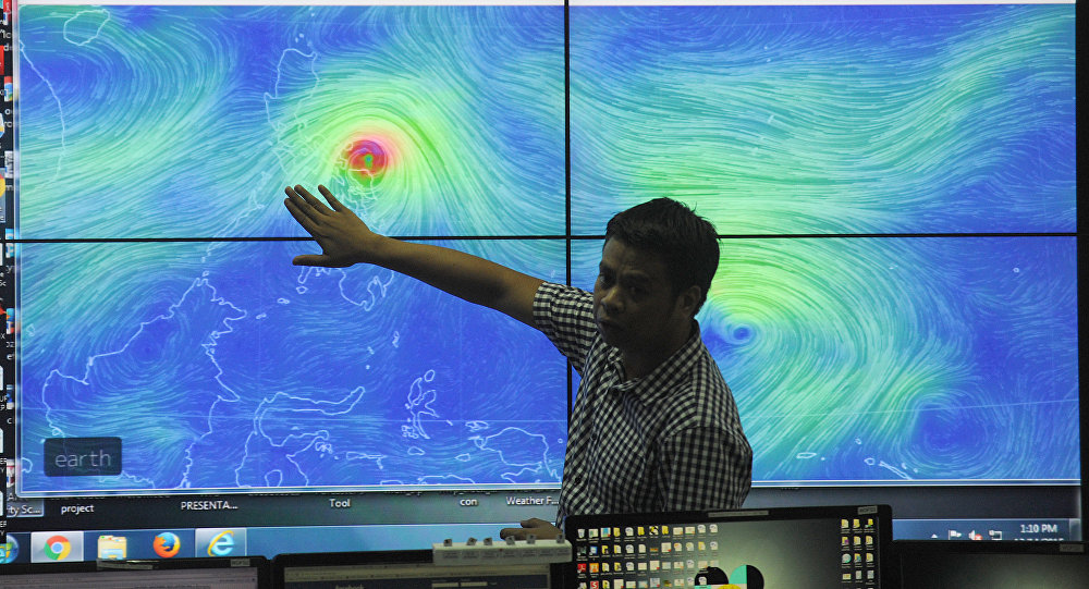 Meteorologists from the Philippine Atmospheric Geophysical and Astronomical Services Administration (PAGASA) monitor and plot the direction of powerful Typhoon Melor at their headquarters in suburban Manila on December 14, 2015.