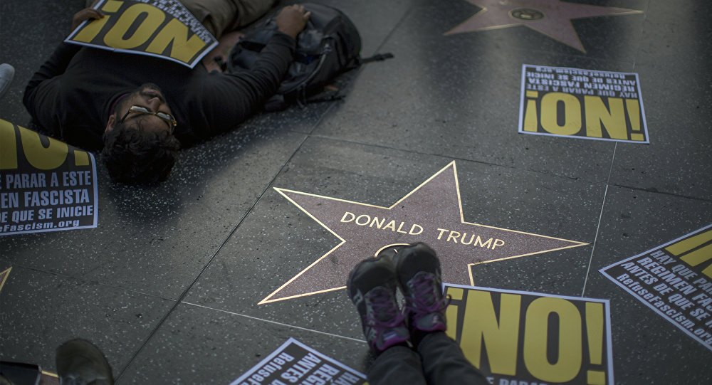 People hold a die-in protest at the Hollywood Walk of Fame star for Donald Trump on Christmas Day in reaction against a Twitter post by US President-elect Trump referring to expansion of the United States nuclear arsenal on December 25 in Los Angeles, California
