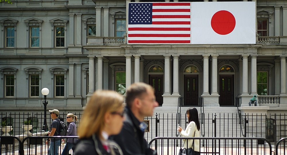 Pedestrians pass infront of US and Japan flags on the Eisenhower Executive Office Building next to the White House on April 27, 2015 in Washington, DC