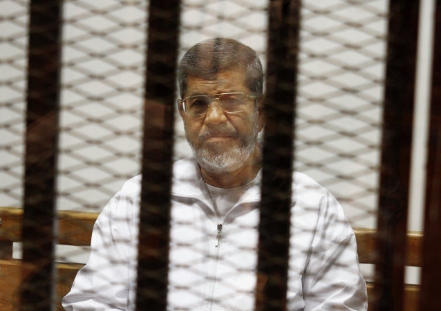 Egypt's ousted Islamist President Mohammed Morsi sits in a defendant cage in the Police Academy courthouse in Cairo, Egypt