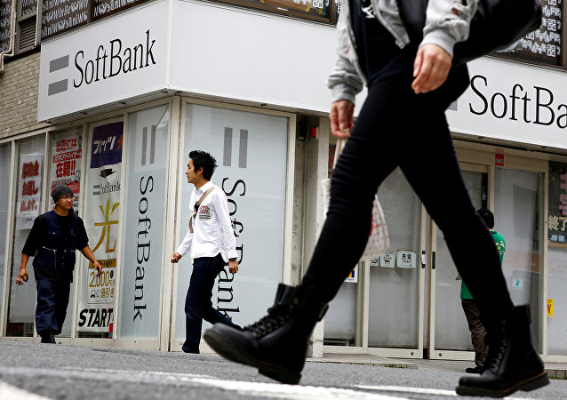 People walk past a retail shop of the SoftBank telecommunications company in Tokyo, Japan