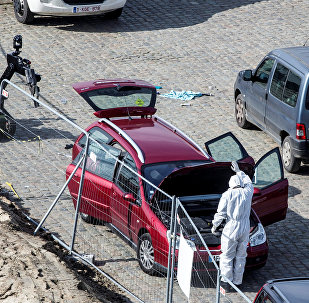 A forensics expert stands next to a car which had entered the main pedestrian shopping street in the city at high speed, in Antwerp, Belgium