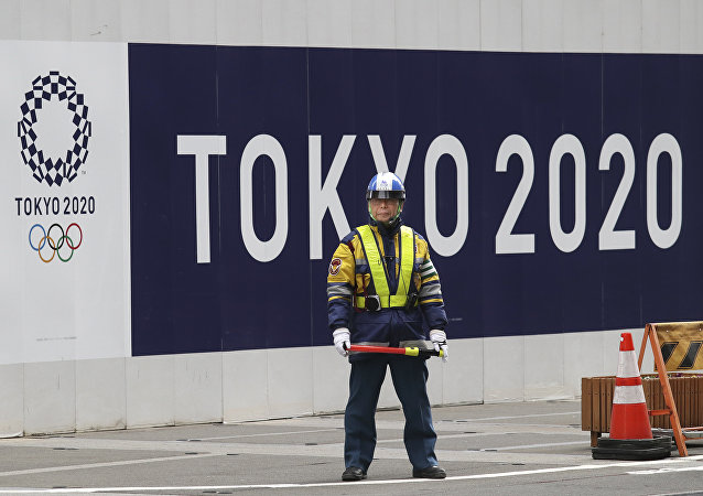 A security guard stands in front of an official logo of the 2020 Tokyo Olympic Games on the safety wall at a construction site in Tokyo's Nihonbashi shopping and office district, Monday, Feb. 6, 2017