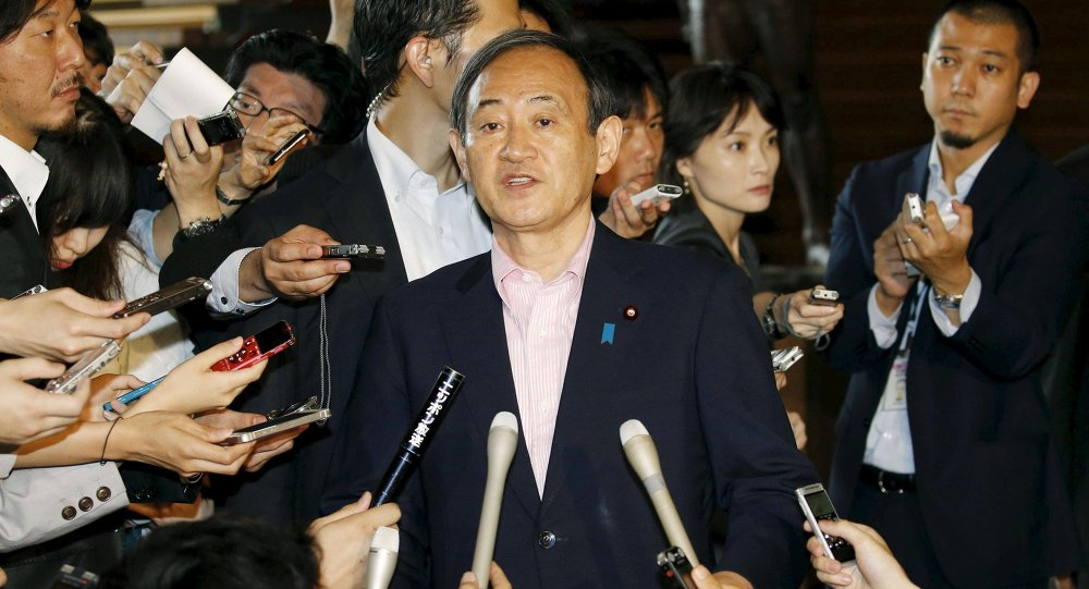 Japan's Chief Cabinet Secretary Yoshihide Suga (C) is surrounded by reporters as he holds an emergency news conference following the eruption of a volcano in southern Japan, at prime minister Shinzo Abe's official residence in Tokyo, in this photo taken by Kyodo May 29, 2015